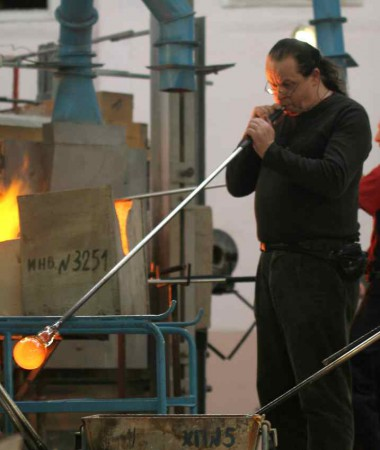 An early stage in the glass blowing process is to blow through a special rod to form the basic shape of the work. Photo courtesy of Jiri Suhajek.